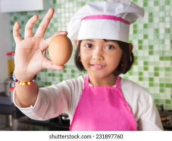 Asian Little Girl with chef dress holding one egg