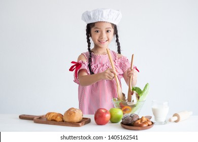 Asian little girl cooking in kitchen on white background