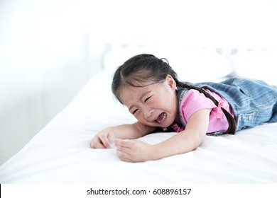 Asian little girl crying on bed on white room background