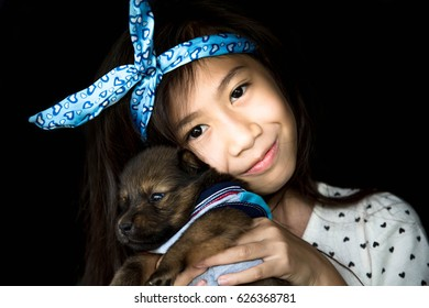 Asian little girl with cute puppy,Friend and love