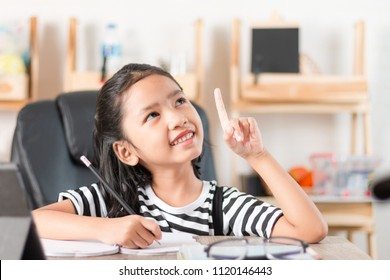 Asian little girl doing homework and pointing finger on wooden table select focus shallow depth of field