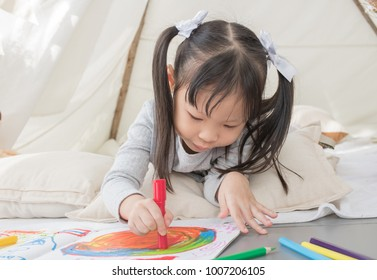 Asian little girl drawing and painting color on notebook in a white room