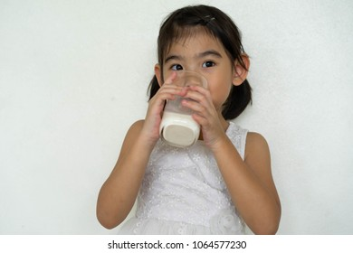Asian little girl drinking milk In a glass
