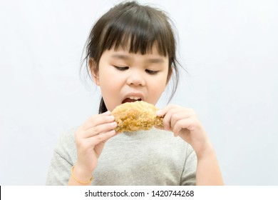 Asian little girl eating chicken drumstick white background. Asia child pick up the  fried chicken  into the mouth.