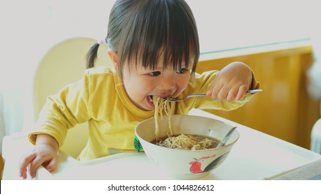 Asian little girl eating delicious thai chicken noodles soup.
