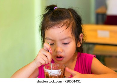 Asian little girl eating ice cream is in an ice cream shop.