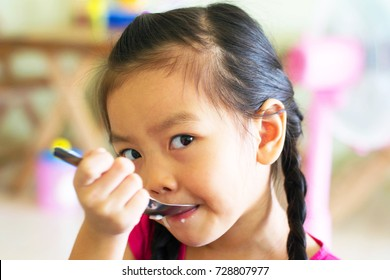 Asian, Little girl is eating rice.