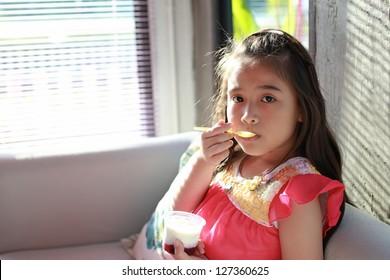 asian little girl eatting yogurt