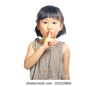 asian little girl finger up to lips for making a quiet gesture isolated on white background