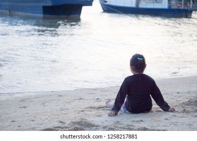 Asian little girl having fun on the beach,playing sand.