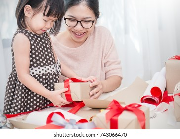 Asian little girl help her mother wrapping gift box, celebration holiday christmas mother'?s day concept.