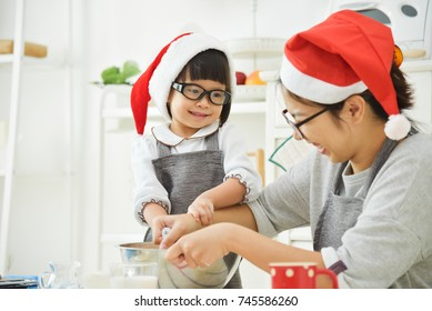 Asian Little girl and her beautiful Young mother wear Santa hats and glasses are preparing the dough for baking cookies in the kitchen. New year and Christmas.