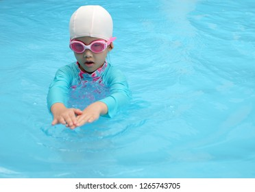 Asian little girl is learning to swim in the pool.