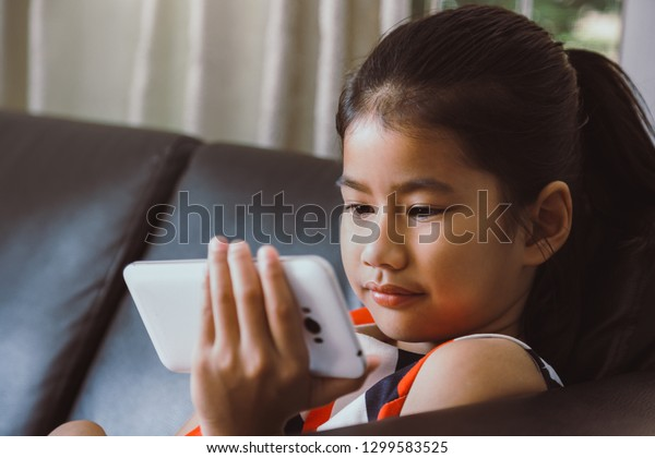Asian little girl looking at mobile phone