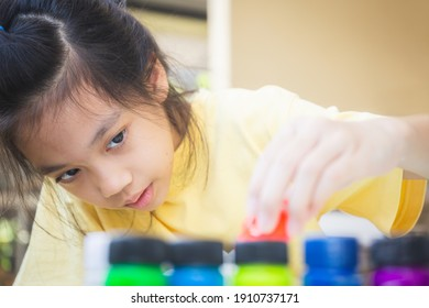 Asian little girl looking and pouring red ink to palette, Creativity children concepts