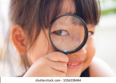Asian little girl looking through magnifying glass