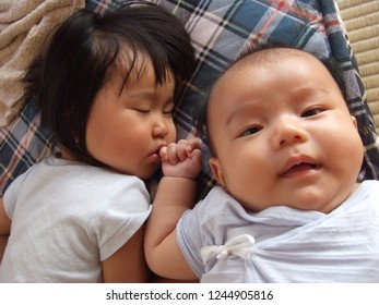 Asian little girl and new born baby taking a nap sleep together brother and sister