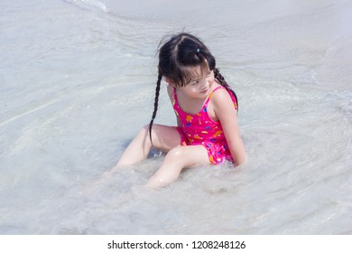 Asian little girl on the beach on blue sea shore in summer vacation.