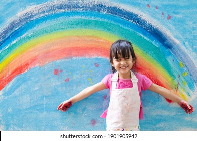 Asian little girl is painting the colorful rainbow and sky on the wall and she look happy and funny, concept of art education and learn through play activity for kid development.