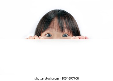 Asian little girl peeping from behind a white table