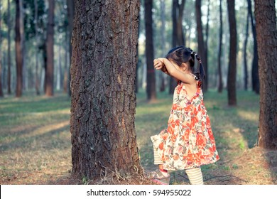 Asian little girl is playing hide-and-seek hiding face in the park