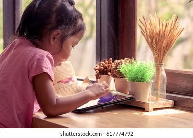 Asian little girl is playing ipad tablet in vintage color tone
