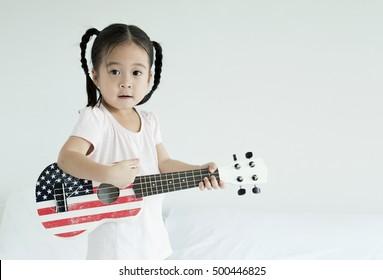 asian little girl plying ukulele in bedroom