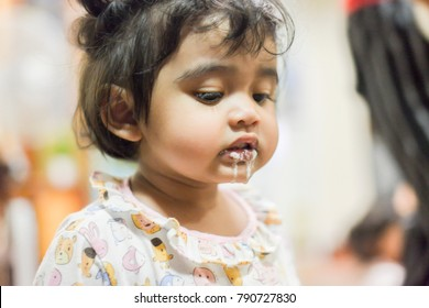 Asian little girl puking,vomiting after drinking milk (Soft focus)