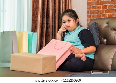 Asian little girl received online shopping parcel opening shopping bag finding order goods is wrong feeling angry and using mobile cell phone calling for store center complaint.