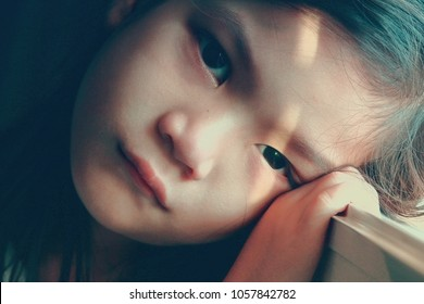 Asian little girl sad by the window while sunset.Girl has red nose and eyes ,She may crying Concept of lonely child or kid in trouble or kid violence.Vintage or retro  color tone.