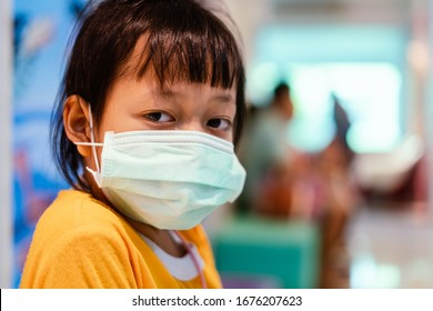 Asian little girl sitting in a hospital and wear  medical mask with sad eyes and hope . Coronavirus Covid-19 concept.
