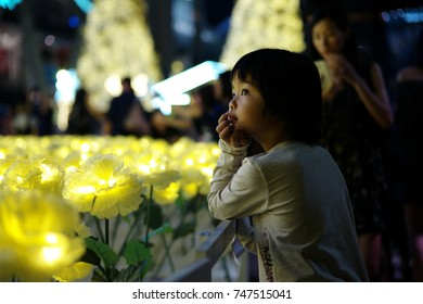 Asian little girl stands in front of the lighting flower at the festival event