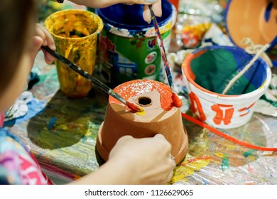 Asian little girl study and learning paint on flower pot in the art classroom of her school.