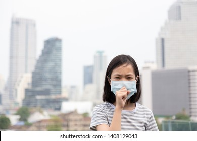 Asian little girl suffer from cough with face mask protection,cute child wearing face mask because of air pollution in the city building,Sick girl with medical mask;concept of pollution,dust allergies