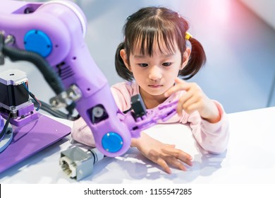 asian little girl touching a robotic machine arm