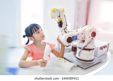 asian little girl touching a robotic machine arm