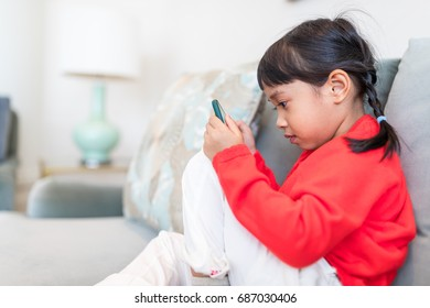 Asian little girl watching on mobile phone