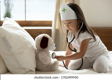 Asian little girl wear medical cap uniform hold phonendoscope listens heartbeat to stuffed toy dog heals best friend takes care of him, healthcare, pediatrician, future profession and vocation concept