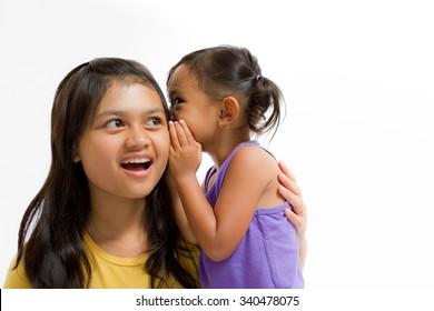 Asian Little Girl Whispering Secret Story to Teen Sister Isolated on White
