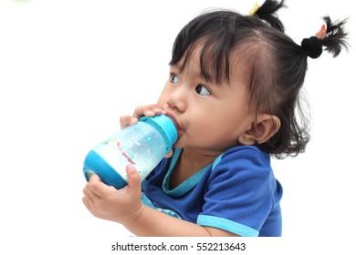 Asian little girls drink milk from bottle on white background