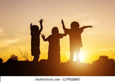 Asian little girls. Silhouette of three children are having fun during sunset.