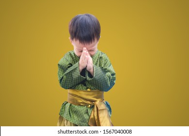 Asian little toddler boy in Thai vintage costume greeting isolated on metallic gold colored background with clipping path. Greeting with hand in Thai tradition called Sawasdee, Soft & Selective focuse