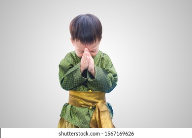 Asian little toddler boy in Thai vintage costume greeting isolated on white gradient background with clipping path. Greeting with hand in Thai tradition called Sawasdee, Soft & Selective focuse