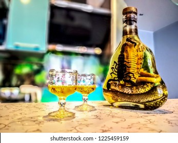 Asian Local Bottle Whiskey and Liquor with Snakes and Scorpions, cambodia. medicinal liquor:  Poisonous animals.  Small wine glasses with liquid, bubbles and alcohol. beautiful background of kitchen