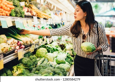 asian local woman buy vegetables and fruits in supermarket. young chinese lady holding green leaf vegetable and picking choosing green onion on cold open refrigerator. elegant female grocery shopping