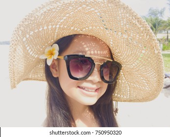 Asian long black hair girl is smiling and wearing black sunglasses, straw hat and white flower behind the right ear. The face of the girl has light and shadow caused by the light through the hat.