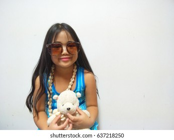 Asian long black haired girl wearing a blue skirt wearing brown glasses carrying a white teddy bear smiling happily on a white background.