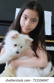 Asian long haired girl holding a white dog with a black piano background.