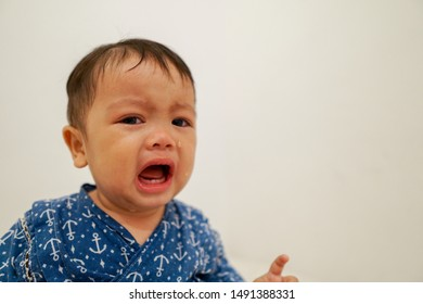 An asian looking little boy unhappy facial expressions, and crying inconsolably.