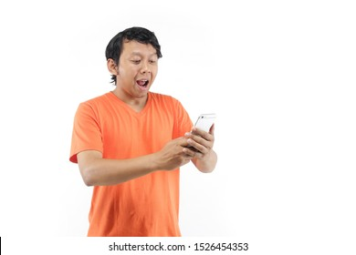 asian looking phone surprised. indonesia man with smartphone using orange t-shirt.